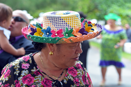 RAROTONGA - DEC 18 2017:Cook Islander woman wearing a Rito hat. Rito hats are worn by women to church. They are made from the uncurled immature fibre of the coconut palm and are of very high quality.