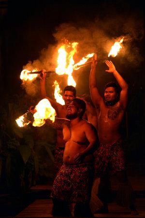 RAROTONGA - JAN 07 2018:Cook Islander men fire dancing in Rarotonga Cook Islands.  The Fire Dance, regularly performed for tourists, have origins in the Pacific Islanders ancient rituals.