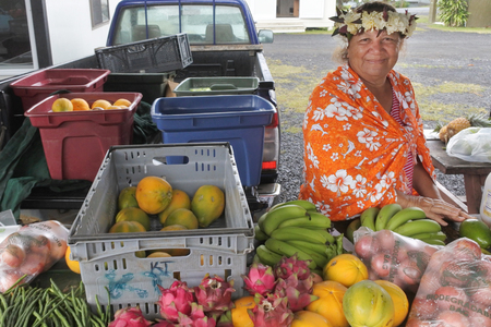 RAROTONGA - JAN 04 2018:A happy Cook Islander woman sale fresh produce at Punanga Nui Market one of the highly regarded traditional markets in the South Pacific and were tourists mix with the locals.
