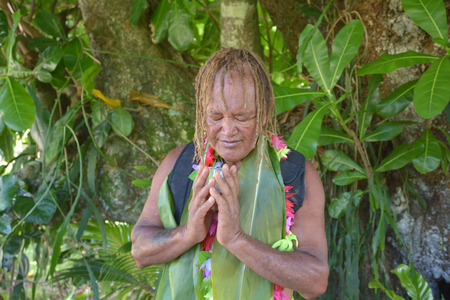 Cook Islander (Pa) blesses on noni juice during an Eco tourism tour in Rarotonga Cook Islands. Real people. Copy space