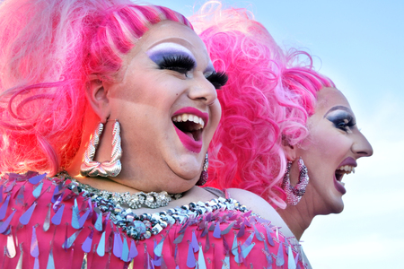Auckland, New Zealand -  Dec 02 2017: Happy drag queens laughing. A drag queen is a male who dresses in clothing of the opposite sex, acts with exaggerated femininity in feminine gender roles for ente 에디토리얼