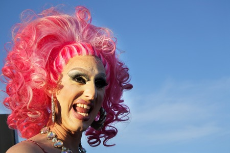 Auckland, New Zealand -  Dec 02 2017: Happy drag queen laughing with a blue sky in the background. Drag queen is a male who dresses in clothing of the opposite sex, acts with exaggerated femininity in 에디토리얼