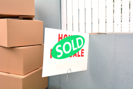 Moving boxes pile beside a home for sale sign with  sold sticker covering it.  Buy, sale, real estate, insurance, mortgage, bank loans and housing market concept. Copy space