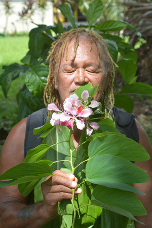 Un anciano isleño del Pacífico (75 años) huele una flor en una gira de turismo ecológico en las Islas Cook de Rarotonga. Gente real. Copie el espacio.