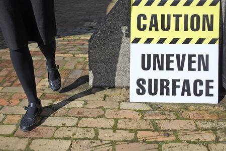 Woman walks beside Caution - Uneven Surface. Danger concept. Copy space