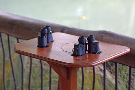 Two binoculars on a wooden table beside a body of water ready for birdwatching activity. Copy space Banco de Imagens