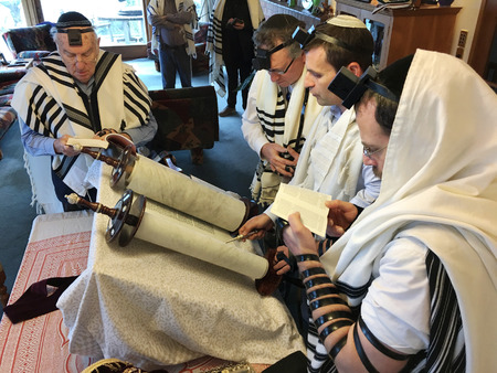 AUCKLAND - JUN 22 2018:Jewish people reading from the Torah Aliyah Blessings during the High Holidays. Reading the Torah is one of the bases for Jewish life.