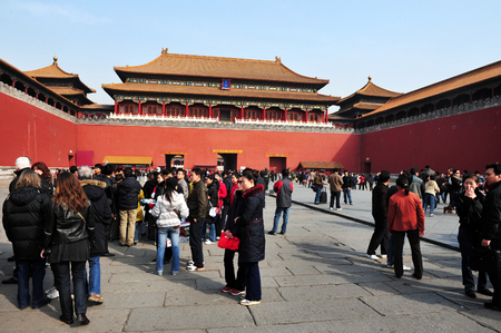 BEIJING - MARCH 11 2009:Tourists at entrance gate of the Forbidden City in Beijing, China. Its Chinas best-preserved imperial palace and is known to be the worlds largest ancient palatial structure.