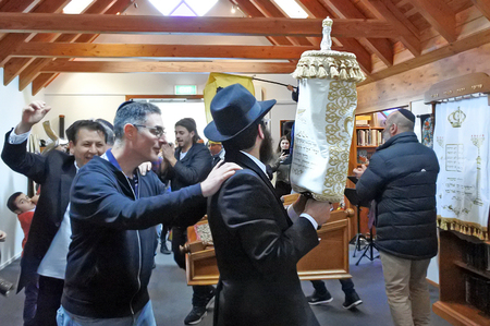 AUCKLAND - SEP 02 2018: Jewish people singing and dancing Inside a synagogue during Inauguration of a new Torah scroll ceremony.It is a handwritten copy of the Torah, the holiest book in Judaism.