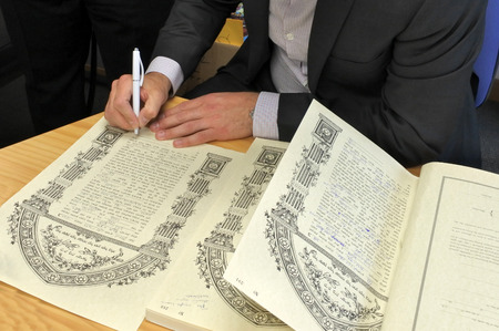 AUCKLAND  - OCT 31 2018:Rabbi signing Ketubah Jewish Prenuptial Agreement document in a traditional Jewish marriage that outlines the rights and responsibilities of the groom, in relation to the bride.