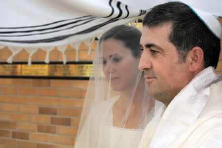 Jewish bride and a bridegroom married in a modern Orthodox Jewish wedding ceremony.