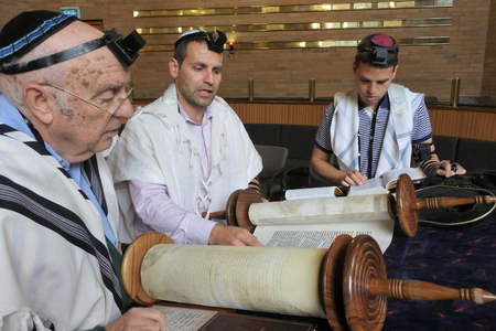 AUCKLAND - NOV 08 2018:Jewish men reading and praying from a Torah scroll. Reading the Torah is one of the bases for Jewish life. Editorial