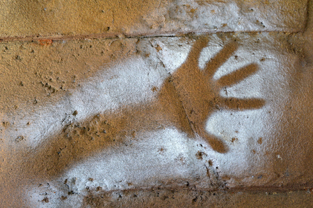 Painted handprint stenciled on a rock
