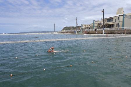 NEWCASTLE, NSW - FEB 2019:Man swiming at Newcastle Ocean Baths.Newcastle Ocean Baths is one of Newcastle New South Wales, Australia outstanding historic landmarks .