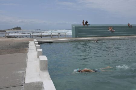 NEWCASTLE, NSW - FEB 2019:People swiming at Newcastle Ocean Baths.Newcastle Ocean Baths is one of Newcastle New South Wales, Australia outstanding historic landmarks .