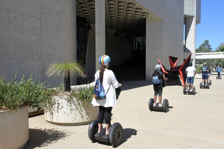 CANBERRA - FEB 22 2019:Tourist riding on Segway outside the National Gallery of Australia in Canberra Australia Capital Territory.It is the national art museum of Australia holding more than 166,000 works of art. Sajtókép