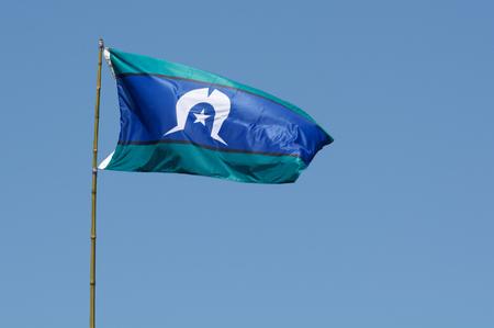 Torres Strait Islander Flag wave against blue sky in Australia. The Torres Strait Islander Flag represents Torres Strait Islander people.