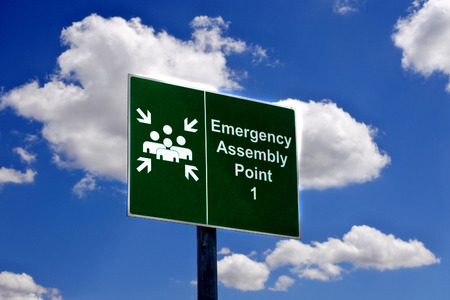 Emergency assembly point one sign against white clouds over blue sky.