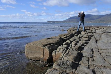 Fotógrafo de viajes fotografiando la vista horizontal del pavimento teselado en Pirates Bay en la Península de Tasmania en Tasmania, Australia