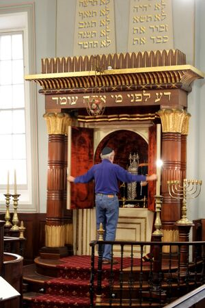Hobart, Tasmania - March 21, 2019: Jewish man opens the Torah ark of Hobart Synagogue. The synagogue is the oldest synagogue building in Australia and is a rare example of the Egyptian Revival style of synagogue architecture