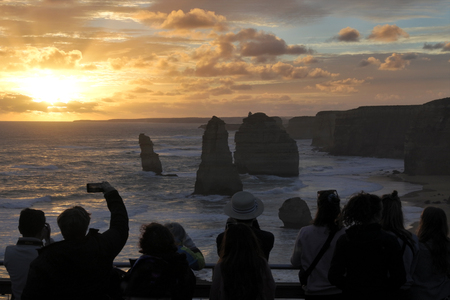 Silhouette of unrecognizable tourists at Port Campbell National Park, looking at the Twelve Apostles during sunset along the Great Ocean Road in Victoria, Australia. Stock Photo