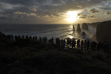 Silhouette of unrecognizable tourists at Port Campbell National Park, looking at the Twelve Apostles during sunset along the Great Ocean Road in Victoria, Australia. Imagens