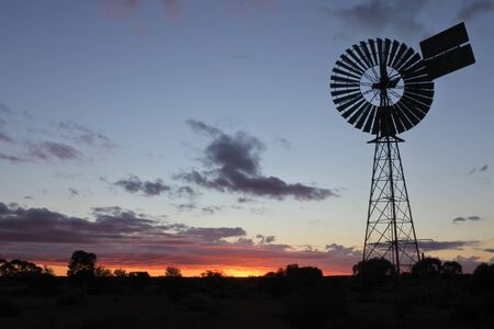 Silhouette of a large windmill in central Australia outback during a dramatic sunset.