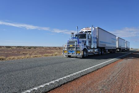 Coober Pedy, South Australia - May 20 2019: Three-trailer road train driving in central Australia Outback.Road train is a trucking vehicle used in remote areas of Australia,USA and Europe to move freight efficiently.