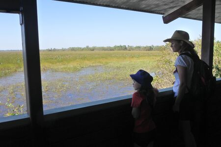 Australian mother and daughter looking a the landscape view of wetland swamp in Kakadu National Park Northern Territory Australia 新聞圖片