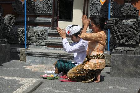 Ubud, Bali, Indonesia - July 24 2019:Balinese family celebrating Galungan Kuningan holidays in a family temple in Ubud Bali, Indonesia.