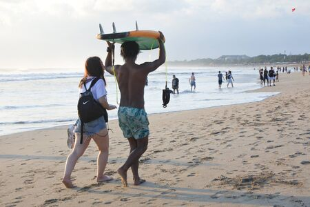 Bali, Indonesia - July 23 2019:Japanese woman and Balinese male gigolo walking on Kuta beach.Balis beaches are renowned for their male gigolos and Japanese Women travel to Bali for sex with local beach boys.