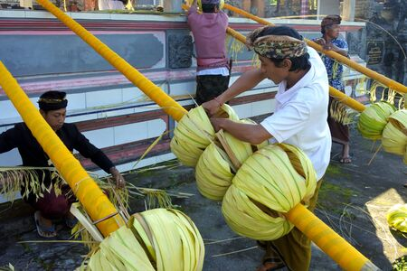 Bali, Indonesia - July 28 2019:Balinese men preparing Traditional Bali Penjor bamboo pole with decoration in a temples in Bali Indonesia on Galungan Kuningan holidays