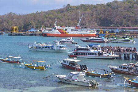 Bali, Indonesia - July 29 2019:Tourist boarding a fast boat ferry to Gili Islands on Padang Bai Harbour Port in Bali Island Indonesia. Padang Bai is a transportation hub between Bali and Lombok Islands. 新聞圖片