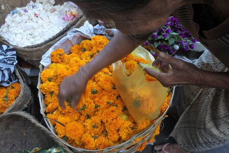 Bali, Indonesia - July 25 2019:Balinese woman buying marigold flowers for offering at Ubud Market in Bali Indonesia.Balinese culture is a mix of Balinese Hindu-Buddhist religion and Balinese customs. 新聞圖片