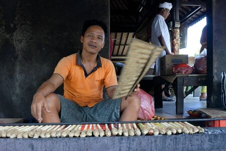 Bali, Indonesia - July 29 2019:Indonesian man grilling chicken satay skewers in Bali Indonesia. Satay originated in Indonesia and became popular in Malaysia, Singapore, Thailand, and Brunei.