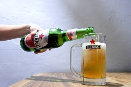 Bali, Indonesia - July 28 2019:Person drinking Bintang Beer Bali Indonesia.Bir Bintang brand was awarded as Top 50 Most Valuable Indonesian Brand 2013 by Brand Finance.