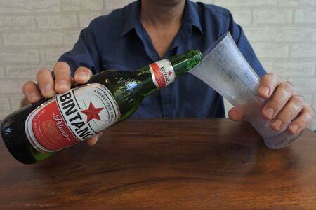 Bali, Indonesia - July 27 2019:Man drinking Bintang Beer Bali Indonesia. Bir Bintang brand was awarded as Top 50 Most Valuable Indonesian Brand 2013 by Brand Finance.