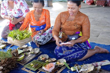 Bali, Indonesia - July 28 2019:Balinese women preparing Traditional Hindu offering decoration outdoors for temples in Bali Indonesia on Galungan Kuningan holidays.
