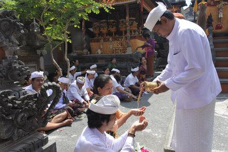 Ubud, Bali, Indonesia - July 24 2019:Hindu priest blessing Balinese family celebrating Galungan Kuningan holidays in a family temple in Ubud Bali, Indonesia.