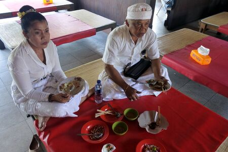 Bali, Indonesia - July 29 2019:Indonesian couple eating traditional Indonesian food in a restaurant in Bali Indonesia. Indonesia has around 5,350 traditional recipes, with 30 of them considered the most important