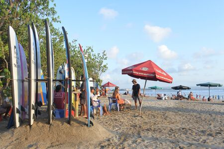 Bali, Indonesia - July 23 2019:Tourists on Kuta Beach. Kuta is where the modern era of tourism in Bali began. It is known for its long sandy beach and great waves for surfing.