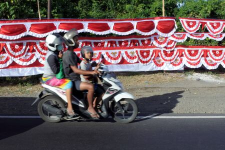 Bali, Indonesia - August 04 2019:Indonesian family riding on a scooter against Indonesia national flags ready for Indonesia Independence Day. Indonesias Proclamation of Independence on 17 August 1945.