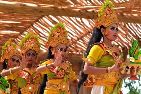 Balinese women dancing Tari Pendet Dance. Pendet is a traditional dance from Bali, Indonesia, in which floral offerings are made to purify the temple as a prelude to ceremonies. Stock Photo