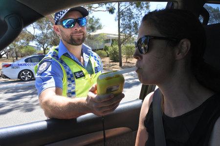 PERTH, WA - 27 DE OCTUBRE DE 2019: Oficial de policía de tráfico australiano con alcoholímetro en la mujer conductora durante las pruebas de sobriedad de campo.Los accidentes de tráfico son causados principalmente por la conducción deteriorada