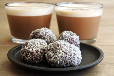 Sweet homemade Chocolate balls served with two cups of cappuccino drinks in a cafe. No people. Copy space