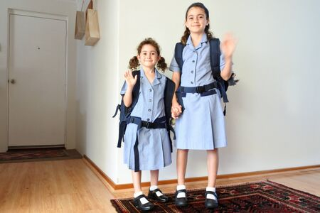 Two happy sisters (age 10 and 6) looking at camera and waving goodbye to parents before going to school together. Indoor home. Real people. Copy space