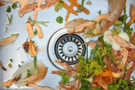 Flat lay view of mix of vegetables waste in home kitchen sink. Food background and texture