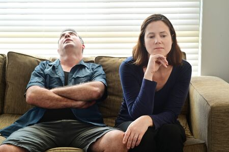 Sad adult couple forced to stay at home as the pandemic coronavirus (COVID-19) forces many people to stay at home because new government policies. Real people. Copy space