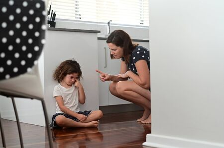 Mother telling off and discipline naughty daughter (age 6) in home kitchen.