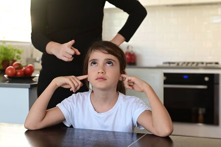 Naughty daughter (age 10) covering her ears while mother telling off and try to discipline her.